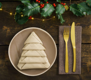Christmas place setting with golden silverware, holly, fairy lights and a napkin folded as a Christmas tree
